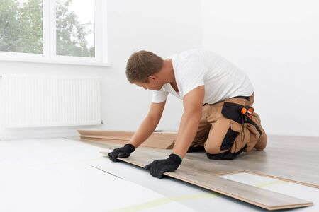Male worker installing laminate flooring. Longitudinal lock joint - The sequence of technological methods for laying and installation of floating flooring - laminate - professional work