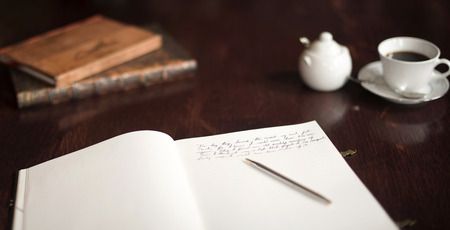 Writing a book with pen on paper pad, coffe and sugar bowl in the distance. Reference books close at hand. Stockfoto