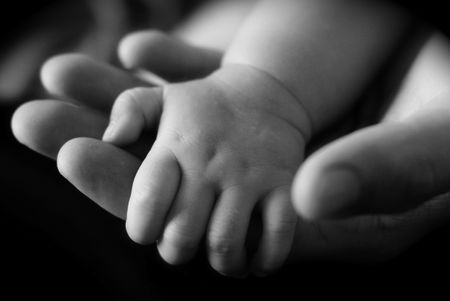 mum and baby: Babys hand holding Adults hand Stock Photo