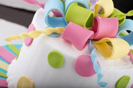 Colorfully Decorated White Birthday Cake Closeup with Fondant Icing Swirls Stock Photo