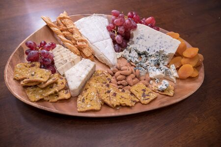 Wooden cheese platter with brie, assorted cheeses, red grapes, crackers and nuts