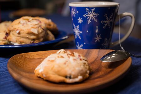 Iced scone with holiday cup of tea and platter of scones in background Stock Photo