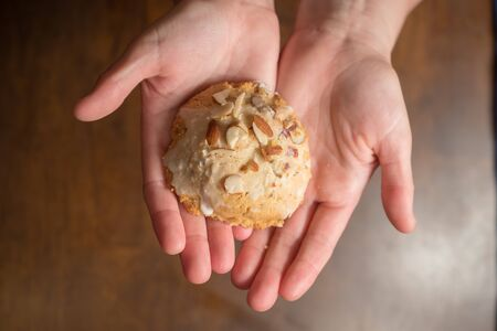 female hands holding out iced scone with almond slivers