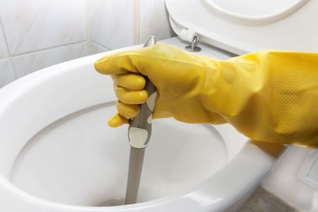 humidify: cleaning toilets in a yellow glove