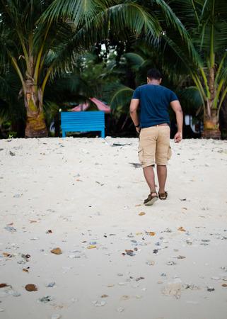 Man Walking Towards a Bench on a Beach