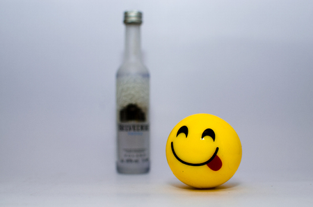 Yellow smiley showing tongue on a white background with a liquor bottle behind