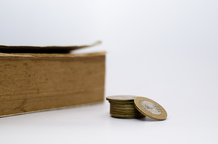 Old books at the background and Money denominations in the foreground symbolizing education and expensive education Stock Photo