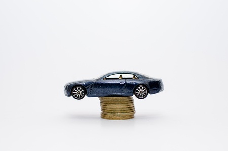 Car mounted on top of pile of coins or denominations symbolizing rise in car prices Stock Photo