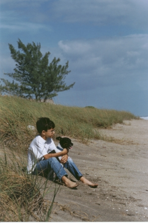 Boy sitting with his dog on the shoreline of the beach in sunny South Florida photo