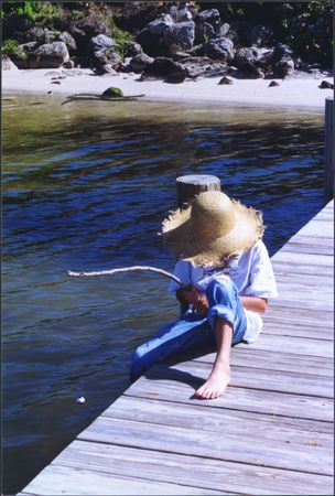 Boy sitting and relaxing while fishing on a dock photo