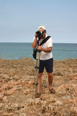beach hunk: Camera Man standing on rocks at the shoreline of a beach on the east coast of South Florida