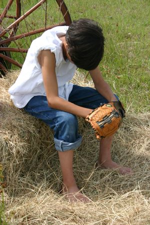 Boy sitting and looking down at his baseball glove photo