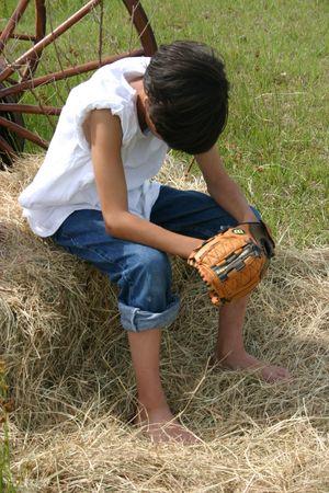 Jongen zitten en zoekt tijdens zijn honkbal handschoen
