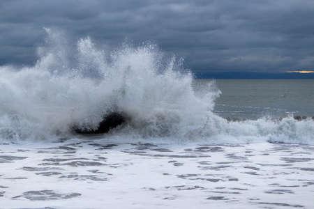 Big waves crashing on a rock at Sandcut Beach in Jordan River Regional Park, British Columbia, Canada