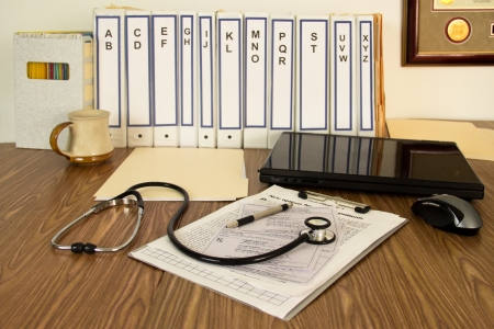 Notebooks, files, laptop, presciptions, coffee cup and stethoscope fill the desktop of a doctor