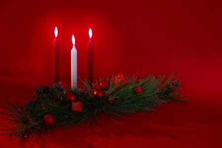 laden: Against a red background, three candles stand behind pine boughs laden with pine cones, Christmas balls and tiny presents  Stock Photo
