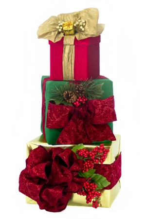 A gold foil-wrapped gift topped by a red damask bow, a green-wrapped gift topped by a red damask bow and a red damask gift topped by gold paper ribbons and bow are stacked one upon another.