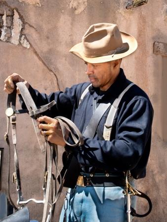 Een van de New Buffalo Soldiers inspecteert zadel versnelling in het Santa Clarita, Californië Cowboy Festival.