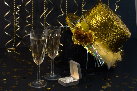 Two flutes of champagne, streamers ,glittery party hats and an engagement ring  wait for the party to begin!