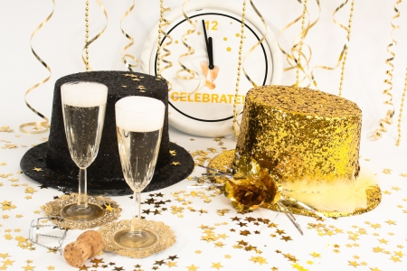 Two flutes of champagne, streamers  and glittery party hats  wait for the clock to reach midnight. Archivio Fotografico
