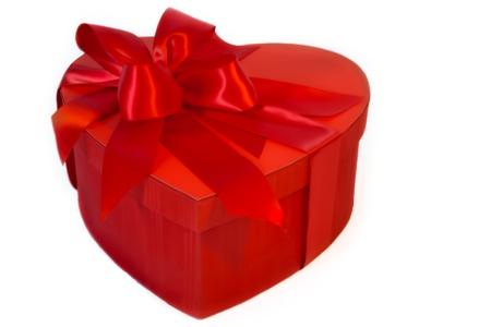 A Valentines Day  heart-shaped box has red satin ribbons and bows.