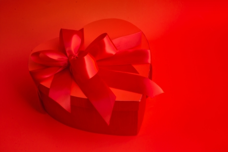 A Valentines Day  heart-shaped box has satin red ribbons and bows.