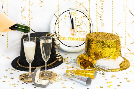 The clock has almost reached midnight and glittered hats, party horns, champagne in flutes and a diamond ring are ready for the celebration. Stock Photo - 15635824
