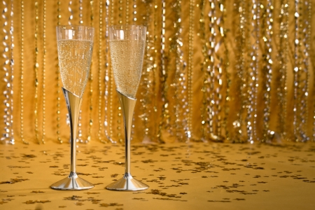 Two silver flutes in front of a shiny, sparkling, festive background hold bubbling champagne. Banco de Imagens
