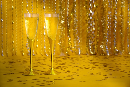 Two flutes of bubbling champagne are against a sparkly background. Banco de Imagens