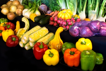 A farmer's market medley of bright vegetables is on a black background. Stok Fotoğraf