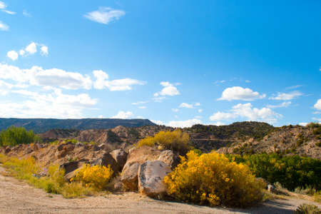 Clouds drift in blue skies above a vista of rocks and colorful native shrubs near Santa Fe, NM  photo
