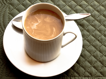 A cup of coffee with swirled milk in a white cup and saucer sits on a green mat.