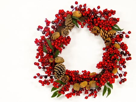 A brown twig wreath is decorated with red   berries and pine cones. Stock Photo - 16048144