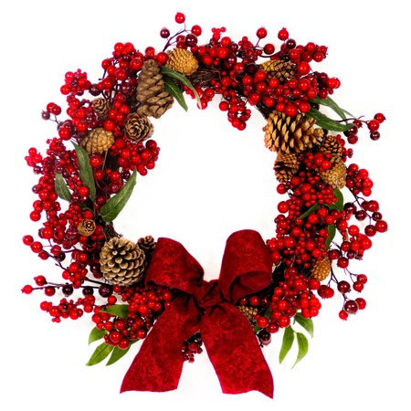 A brown twig wreath is decorated with red berries, pine cones and a red damask bow. Stock Photo