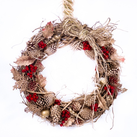 A natural twig wreath is decorated with pine cones, red berries, gold shells and a raffia bow  Stock Photo - 16136924