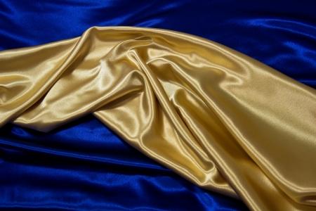 Gold satin material is draped against dark blue satin  Stok Fotoğraf