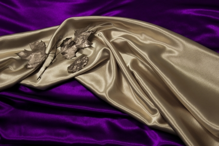 Gold satin material with gold leaves is draped against purple satin  Stok Fotoğraf