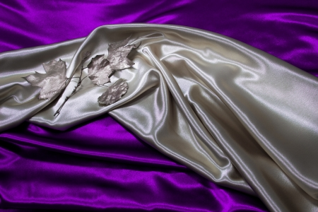 Silver satin material with silver leaves is draped against purple satin