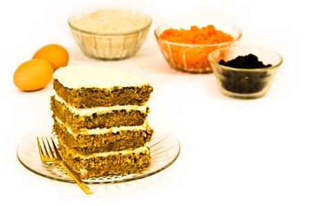 Een stukje carrot cake is omringd door zijn recepteningrediënten