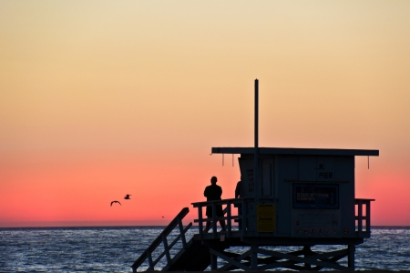 People on a lifeguard tower watch the rosy afterglow of a sunset at Venice Beach, California 版權商用圖片