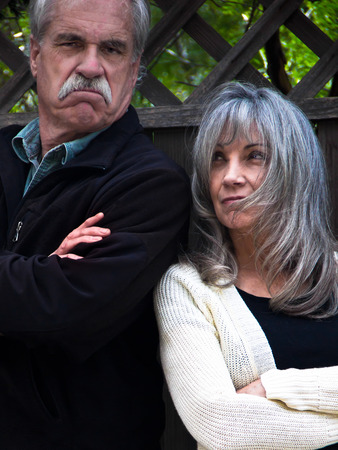 glaring: An angry man and woman stand glaring with arms crossed
