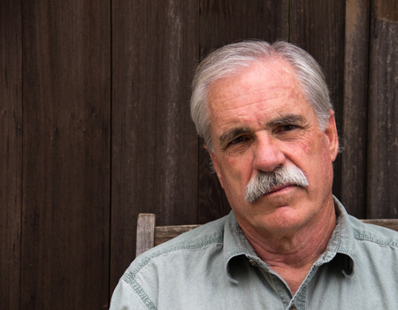 distinguished: A distinguished gentleman in a blue shirt has a serious look  Stock Photo
