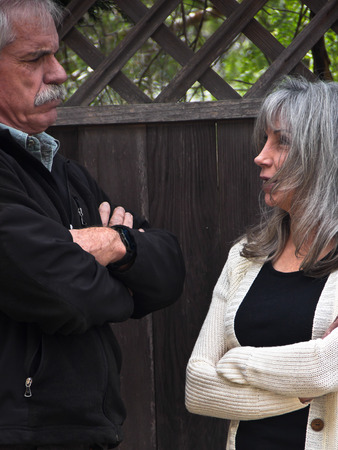 glaring: An angry man and woman stand glaring at each other with arms crossed.
