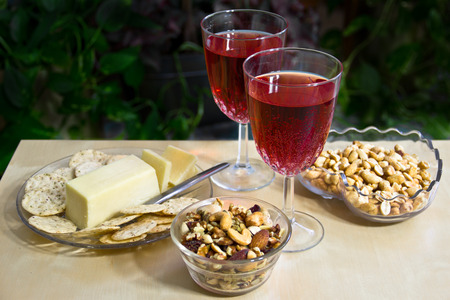 Glasses of wine with cheese, crackers and nuts are set against a greenery background