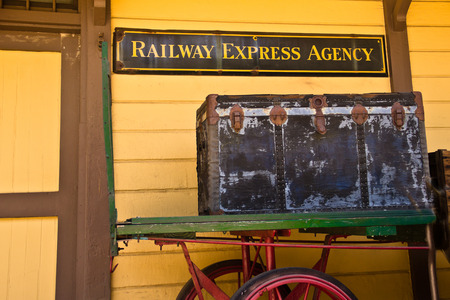 An old railway express trunk sits on an antique cart outside a historic train station in California. Reklamní fotografie