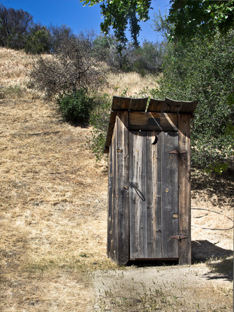 A little outhouse with a crescent moon sits in a rustic park.