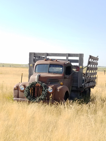Antique Abandoned Truck in a Field with Wreath on Front