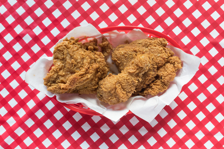 Fried chicken basket with plate on red checkerboard tablecloth
