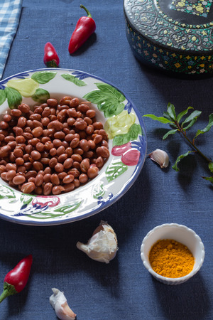 borlotti beans: borlotti beans in a bowl with turmeric, red chillis and garlic, on a blue table cloth,