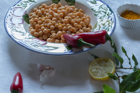 vegetable tin: chickpeas in a bowl with turmeric, red chillis, lemon and garlic, on a white table cloth, Stock Photo